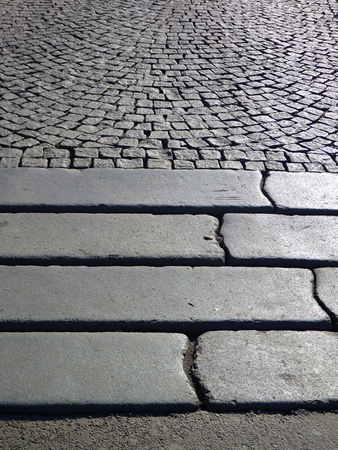 intersect: a detail of steps in a grey paved sidewalk