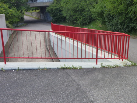an outdoor ramp and staircase with red railing