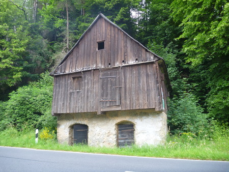 an old wooden house by a road