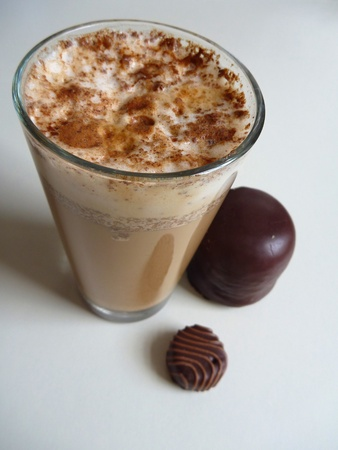 glass of cafe latte with white coam and cream