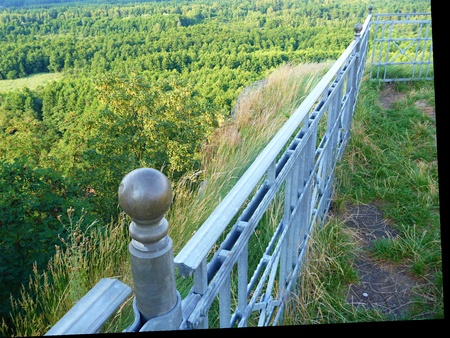a steel railing on the edge of a natural lookout