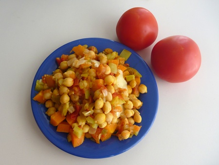 a chickpea vegetable salad on a blue plate Stock Photo