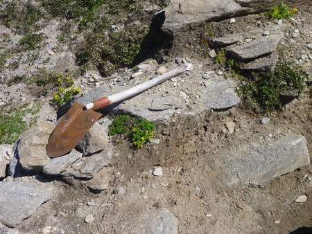 forgotten: a forgotten shovel left on a stony trail