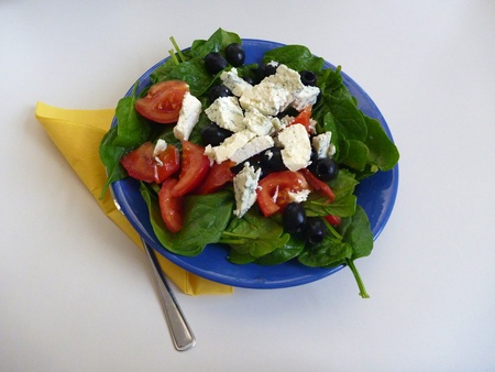 baby goat: a portion od spinach salad with tomatoes and cheese
