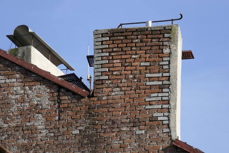 tall chimney: traditional brick chimney on a roof of an old house