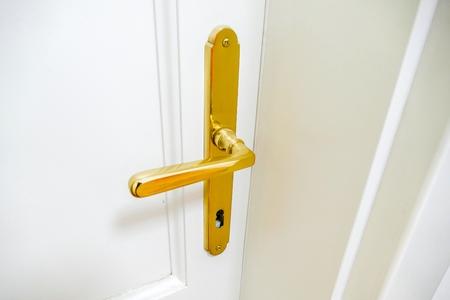 detail van een deurklink in witte deur