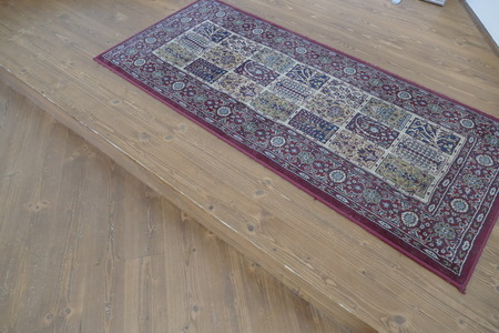 an old carpet on a wooden floor by the door