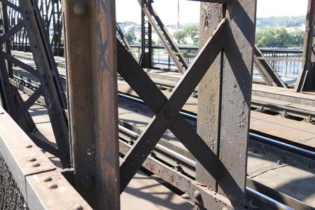 rive: an iron bridge with a pedestrian sidewalk over a river