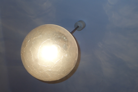 A detail of a decorative round ceiling light shining Stock Photo