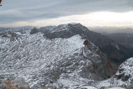 a grey rock with snow in the alps in the early winter