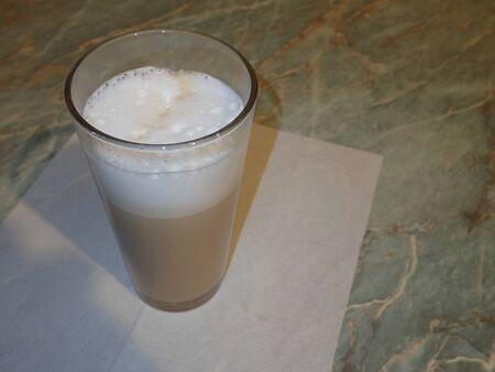 glass of hot cafe latte with creamy milk foam
