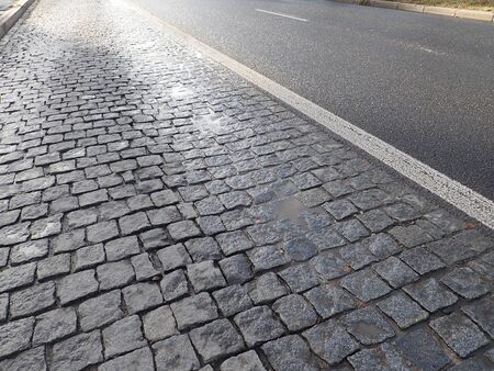grey  cobble pavement texture wet after rain Stock Photo