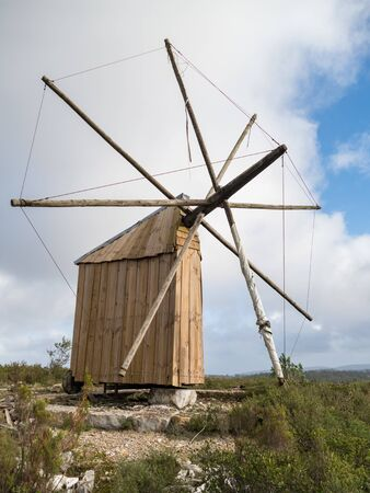 abandoned traditional windmill in a windy landscape in portugal