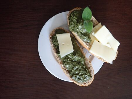 fresh homemade bread with slice of cheese and green pesto 免版税图像