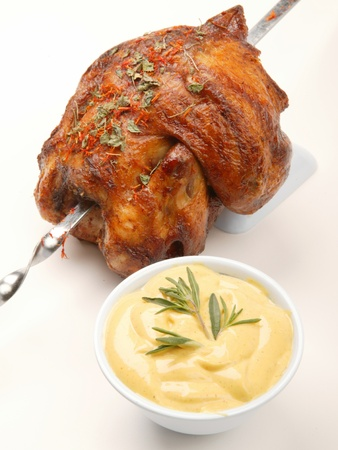 Grilled chicken on spit with herbs and sauce photo