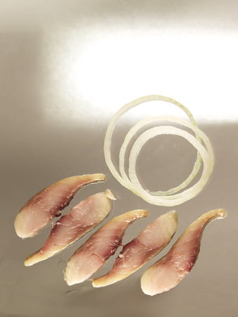 Small slices of salted fresh humpback salmon fillets with onion rings
