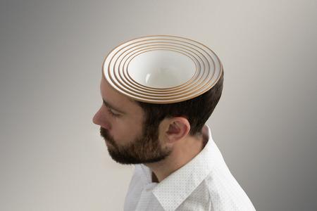 Several ceramic bowls inside a mans head.