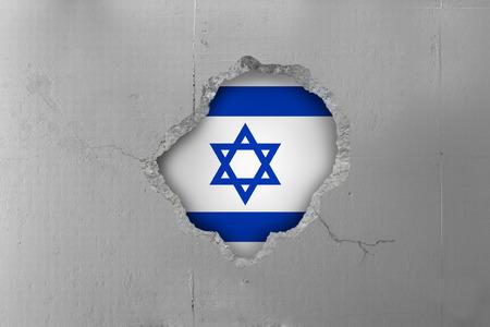 Israeli flag behind a concrete wall.