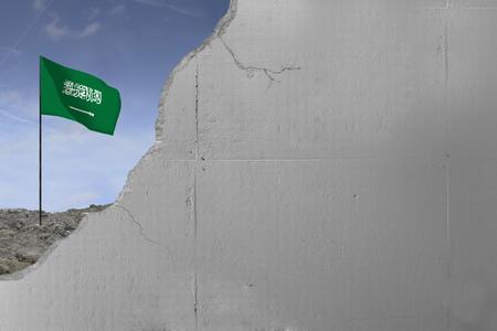 Saudi Arabia flag behind a concrete wall.