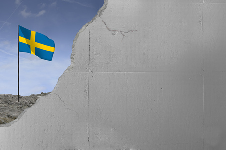 Swedens flag behind a concrete wall.