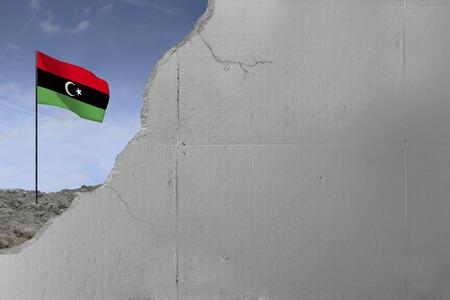 Libyan flag behind a concrete wall.