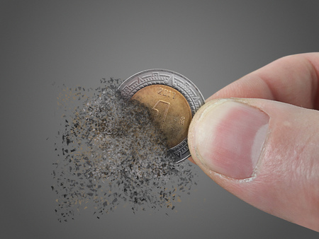 One Peso coin pulverizes in a mans hand.