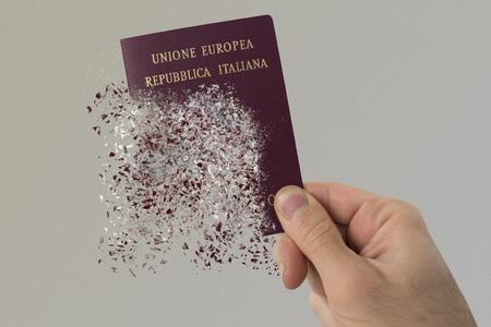 Italian passport pulverizes in a mans hand. Imagens