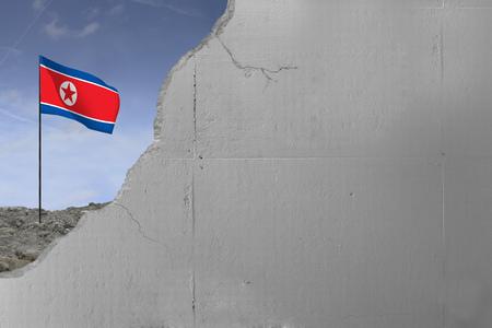 North Korean flag behind a concrete wall. Imagens