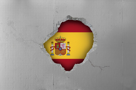 Spanish flag behind a concrete wall. Imagens