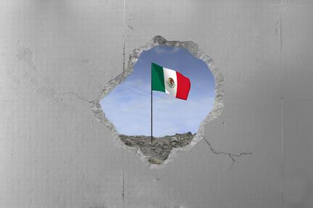 Mexican flag behind a concrete wall.