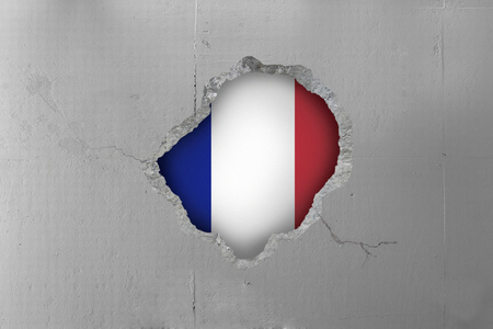 French flag behind a concrete wall. Stock Photo