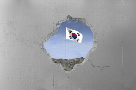 South Korean flag behind a concrete wall.