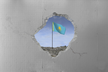 Kazakhstan flag behind a concrete wall.