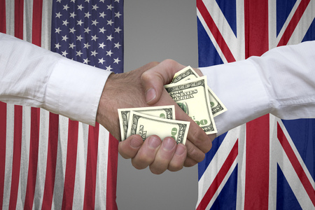 100 dollar bills handshake with USA and UK flags background.