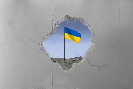 Ukraine flag behind a concrete wall.