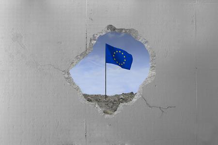 European Union flag behind a concrete wall.