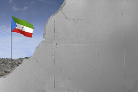 Equatorial Guineas flag behind a concrete wall.