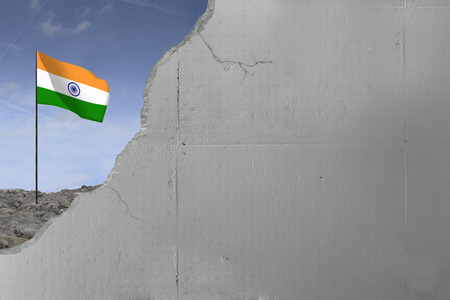 Indian flag behind a concrete wall.
