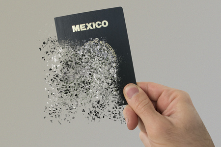 Mexican passport pulverizes in a mans hand. Stock fotó