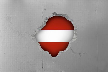 Austrian flag behind a concrete wall.