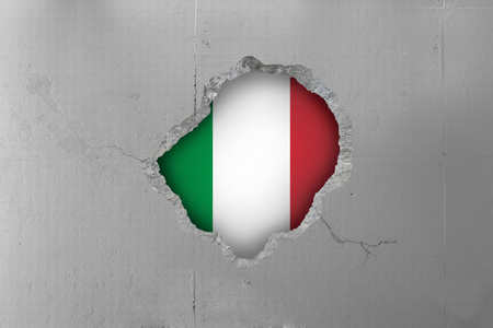 Italian flag behind a concrete wall. Imagens