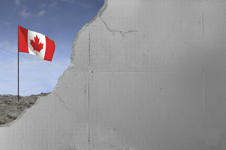 Canadian flag behind a concrete wall.