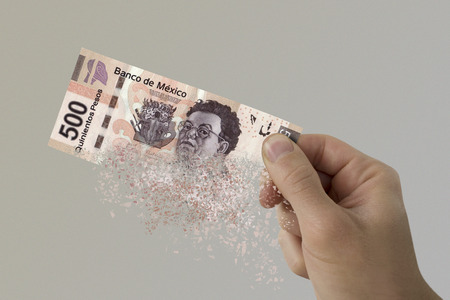 Five hundred Mexican Pesos bill pulverizes in a mans hand.
