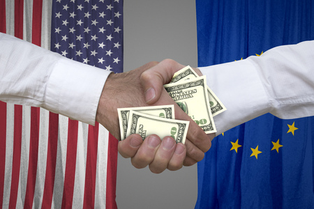 100 dollar bills handshake with USA and Europe flags background.