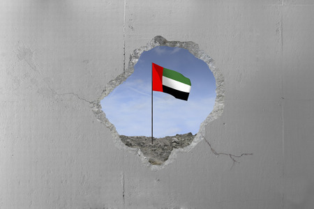 United Arab Emiratess flag behind a concrete wall.