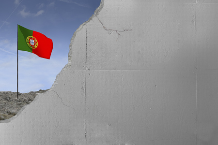 Portugals flag behind a concrete wall.