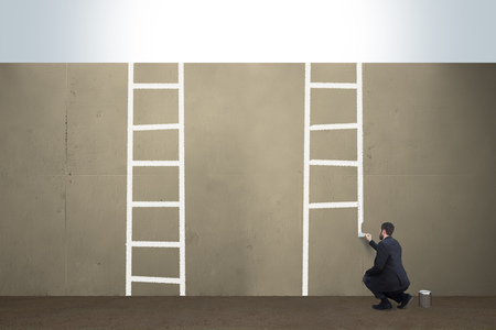 A business man draws ladders on a concrete barrier. Imagens