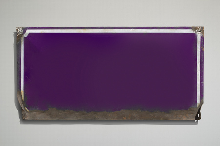 Rusty violet metallic sign with grey background.