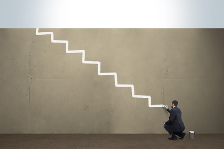 A business man draws stairs on a concrete barrier.