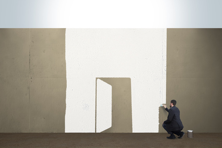 A business man draws a opened door on a concrete barrier.